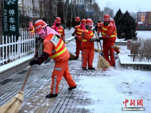 1月3日上午,青海全省有13个测量站出现了降雪。图为西宁环卫工人扫除人行道。中新社记者 孙睿 摄