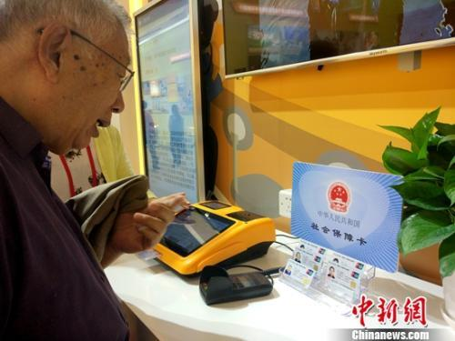 资料图:正在参观社保内容的退休老人。中新网记者 李金磊 摄