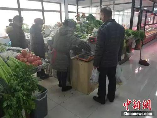 北京市西城区某菜市场内,一名市民使用免费塑料袋买菜。 冷昊阳 摄