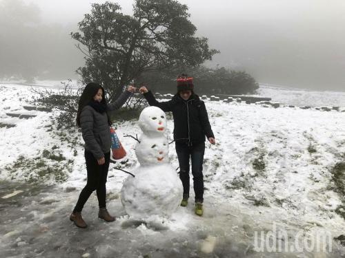 """台北阳明山鞍部5日清晨开始降雪,吸引许多民众上山追雪,雪白一片的景色让追雪民众兴奋不已。图片来源:台湾""""联合新闻网""""。"""