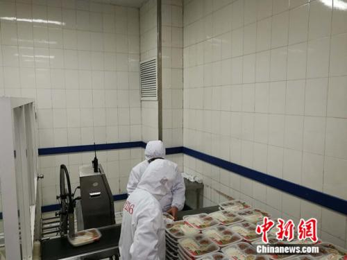 生产车间内工作人员在分拣盒饭。 中新网记者 张尼 摄
