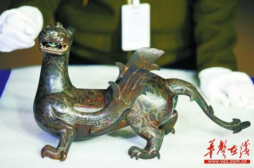 """图为河北省文物研究所藏、1977年河北平山中山国君王墓出土的""""双翼错银铜神兽""""。"""