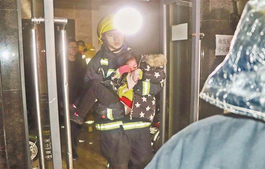 消防员抱着被困的孩子下楼