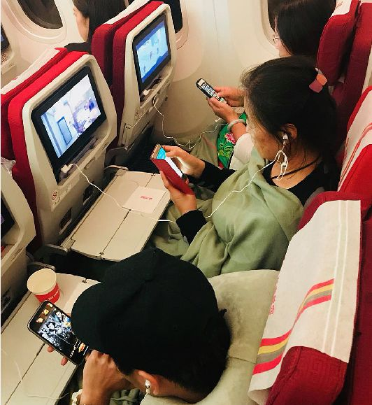 ▲1月18日凌晨,乘坐海航航班的旅客在使用手机。  图/新华社