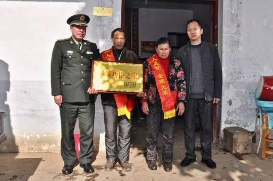 """▲金溪籍军人邓长文的父母手捧功臣牌匾,身披""""一人立功、全家光荣""""红绶带。"""