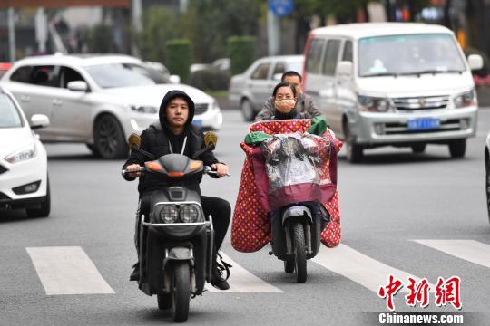 资料图:民众穿上厚衣物骑行。 张浪 摄