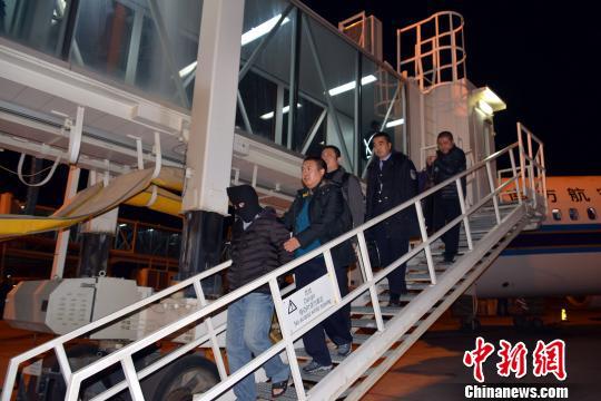 """图为12月8日晚,""""红通""""逃犯杨国庆被兰州警方押解返回兰州。 魏存武 摄"""