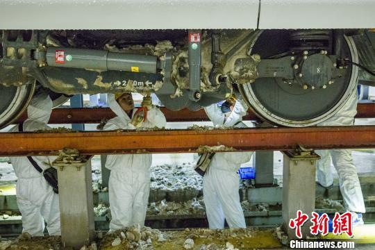 铁路职工用专用工具清理动车车下的积雪积冰。 王曙天 摄