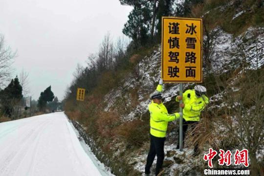 """图为两名交警正在冰雪路段设置""""冰雪路面""""警示标牌。警方供图"""