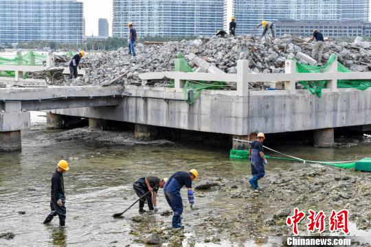 资料图:三亚洲际度假酒店海上餐厅项目拆除,工人正在海水中捡拾落入的建筑垃圾,避免二次污染。 骆云飞 摄