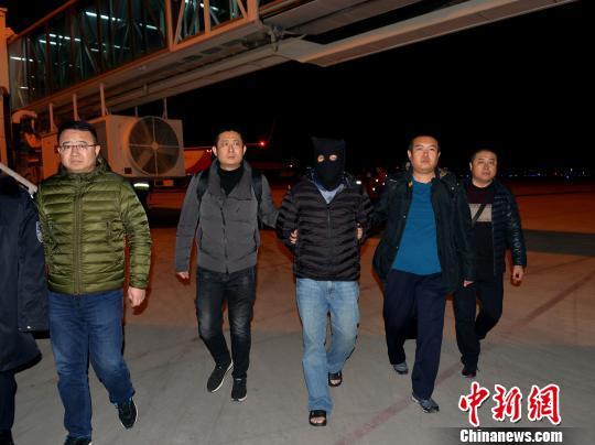 """图为12月8日晚,""""红通""""逃犯杨国庆被兰州警方押解返回兰州。 刘胜男 摄"""