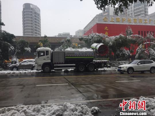 """为除覆盖在大树上的雪,车辆拉着巨型的""""吹风机"""",给树木""""洗剪吹""""。 吴兰 摄"""