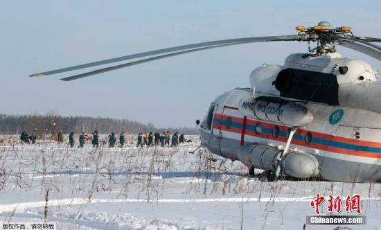 图为当地时间2月12日,俄罗斯紧急情况部工作人员在客机失事地点调查。