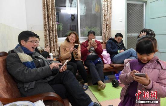 资料图:家人抢手机红包。 中新社记者 吕明 摄