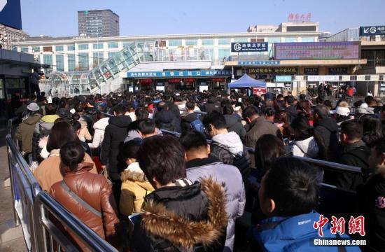2月21日,北京火车站广场上,旅客排队乘坐地铁。 中新社记者 韩海丹 摄