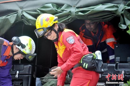 """台湾花莲地震最后两名失联人员2月11日上午被证实罹难。图为11日从地震""""重灾区""""花莲云门翠堤大楼撤离的救援人员。 中新社记者 肖开霖 摄"""