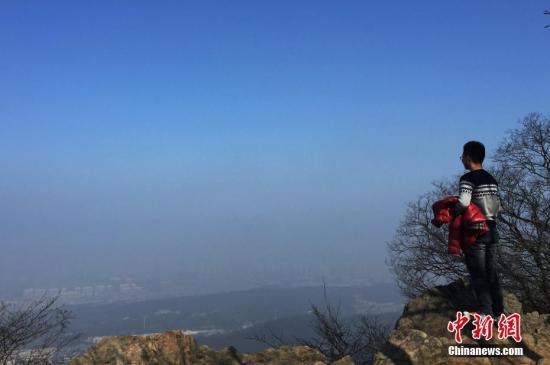 资料图:1月3日,从南京紫金山顶俯瞰,雾霾与蓝天分界明显。中新社记者 泱波 摄