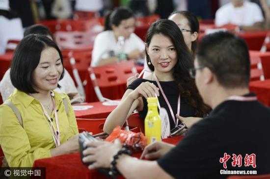 资料图:相亲大会上,男女嘉宾在相互交流。 图片来源:视觉中国