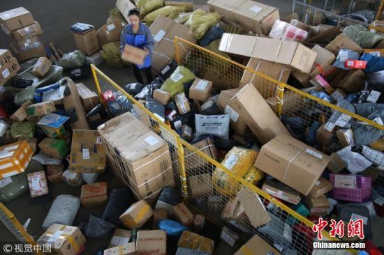 """资料图:""""双十一""""当天,安徽省阜阳市的女快递员张红玲在店内整理快递单据。王彪 摄 图片来源:视觉中国"""