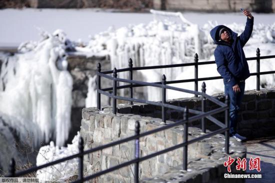 全美日前遭遇极寒天气,多地刷新低温纪录。图为当地时间1月2日,新泽西州东北部城市帕特森的居民Obdulio Arenas举起手机自拍,在他身后是在极寒天气中冻住的瀑布。