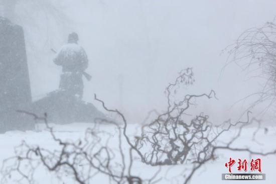 """当地时间1月4日,暴雪中纽约法拉盛公园中的雕塑。当日,纽约降下2018年首场暴雪。受一波被称为""""炸弹气旋""""的风暴影响,美国东北部地区当天普遍遭受暴雪袭扰,3000多个航班因此取消。 中新社记者 廖攀 摄"""