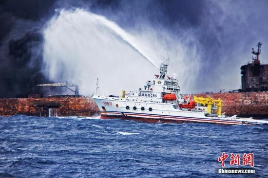 """""""东海救117""""轮向""""桑吉""""轮喷射泡沫降温灭火。1月6日19:51时左右,巴拿马籍油船""""桑吉""""轮与中国香港籍散货船""""长峰水晶""""轮在长江口以东约160海里处发生碰撞。中新社发 上海海上搜救中心供图"""