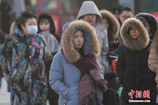 """资料图:冷空气来袭,民众""""全副武装""""出行。中新社记者 武俊杰 摄"""