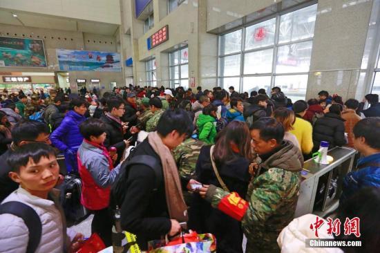 """2月22日,在""""三峡门户""""湖北宜昌,大量返程旅客来到该市火车东站乘车出行,车站联合武警、地方警力、青年志愿者和党团员突击队确保通行顺畅。何强 摄"""
