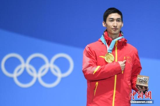 图为武大靖在获颁金牌后手指胸前五星红旗。中新社记者 崔楠 摄