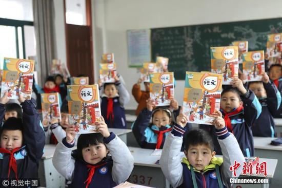 资料图:小学生展示新课本。 万震 摄 图片来源:视觉中国