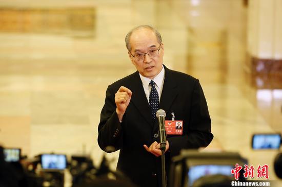 """3月3日,全国政协十三届一次会议在北京人民大会堂开幕。图为司法部部长张军在""""部长通道""""接受记者采访。中新社记者 卞正锋 摄"""