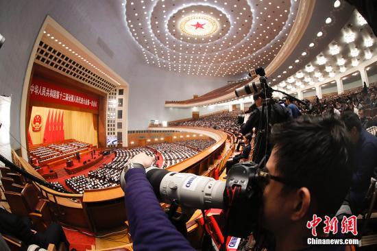 3月13日,十三届全国人大一次会议在北京人民大会堂举行第四次全体会议。图为记者关注会议。 中新社记者 杜洋 摄