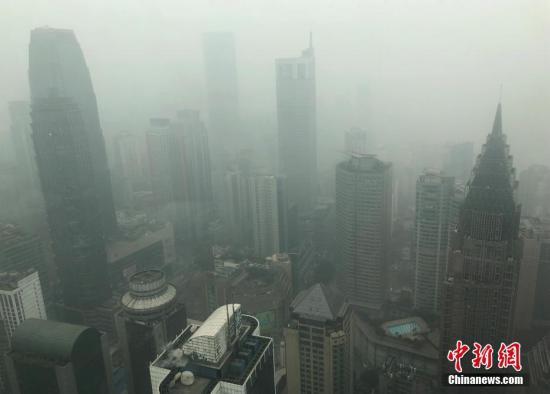 12月28日,重庆主城被大雾笼罩,高楼大厦若隐若现。 中新社记者 周毅 摄