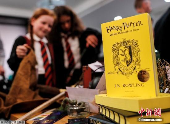 """资料图:2017年6月26日,是风靡世界的魔幻小说《哈利·波特》首部《哈利·波特与魔法石》出版20周年的日子,英国各地""""哈迷""""们举行庆祝活动,为了纪念这个""""魔法世界""""诞生20周年。图为赫奇帕奇特别版《哈利·波特与魔法石》。"""