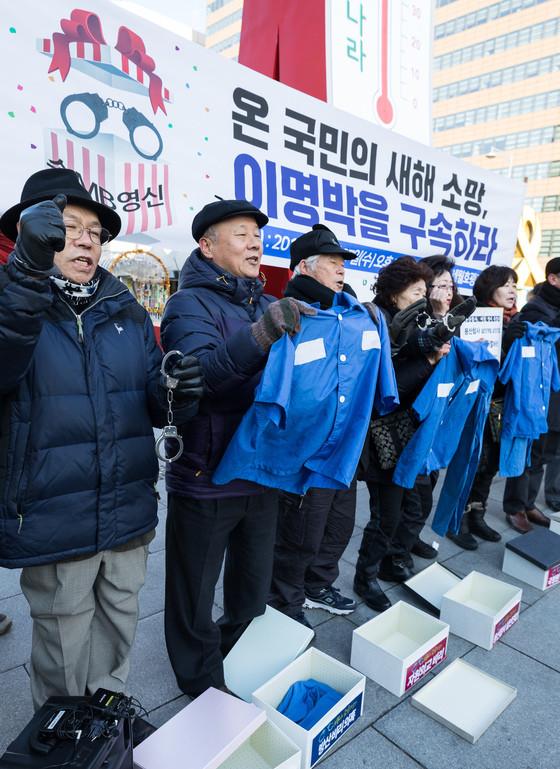 去年12月27日,韩国市民团体手持囚衣要送给李明博