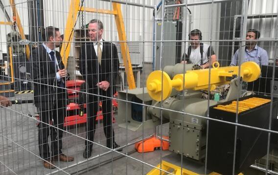 澳大利亚国防工业部长柏恩(左二)在堪培拉一家国防公司考察远程武器系统。(图源:澳大利亚SBS新闻)