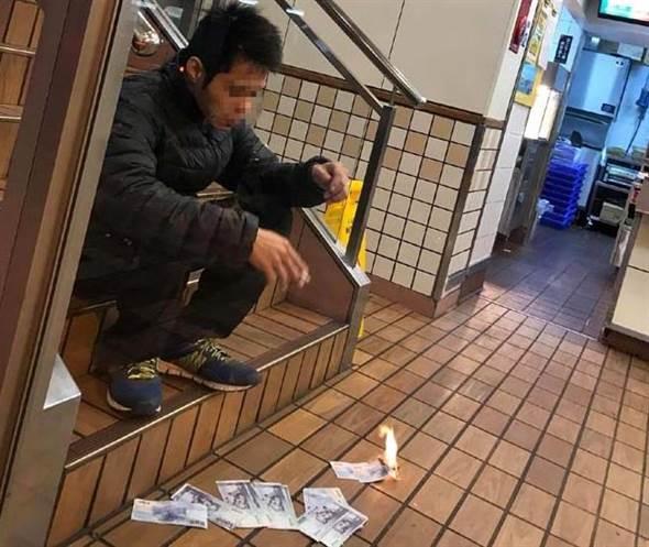 """一台湾男子坐在麦当劳的楼梯上焚烧千元新台币(图片来源:""""中时电子报"""")"""