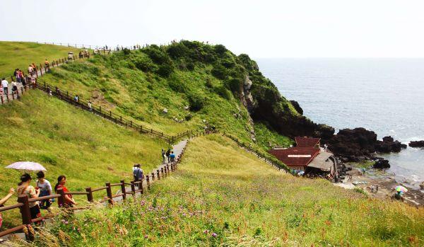 资料图:游客游览韩国济州岛著名景点日出峰。新华社记者姚琪琳摄