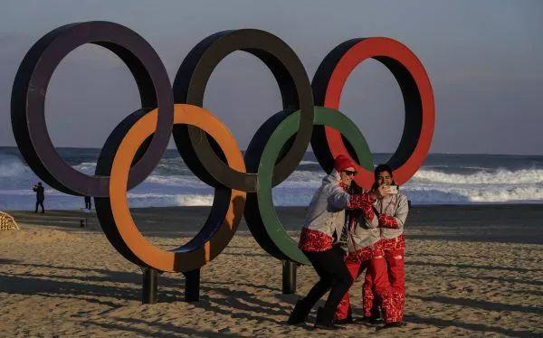 ▲2月4日,在韩国江陵奥运村附近的海滩,人们在奥运五环标志前自拍合影。(新华社)