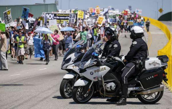 """2017年4月29日,洛杉矶警察在""""人民气候游行""""队伍旁警戒。全美当天举行370多场""""人民气候游行""""反对特朗普气候政策""""开倒车""""。新华社发(赵汉荣摄)"""