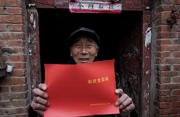 安徽省界首市芦村镇枣林村贫困户喜领脱贫光荣证。东方IC 资料
