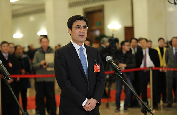 """全国政协委员、国家电网公司董事长舒印彪在经过""""委员通道""""时接受媒体采访。东方IC 图"""