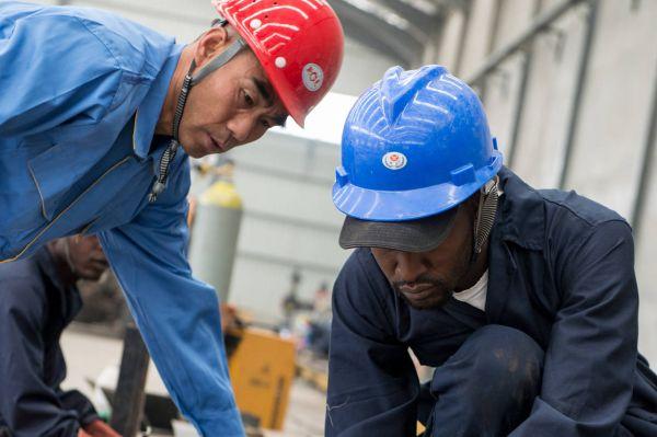 中国工人和肯尼亚工人在中航国际的内罗毕工厂一起组装卡车。(美国《华尔街日报》网站)