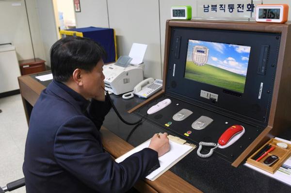 1月3日,在朝鲜半岛中部的板门店,一名韩国官员通过板门店联络热线与朝方通话。新华社 图