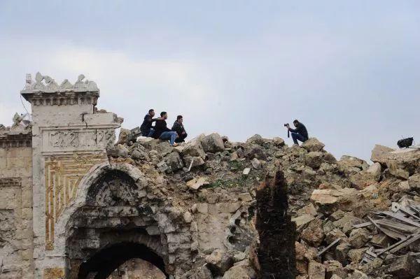 ▲2017年12月17日,在叙利亚阿勒颇老城,几名市民在倭马亚清真寺的废墟上留影。