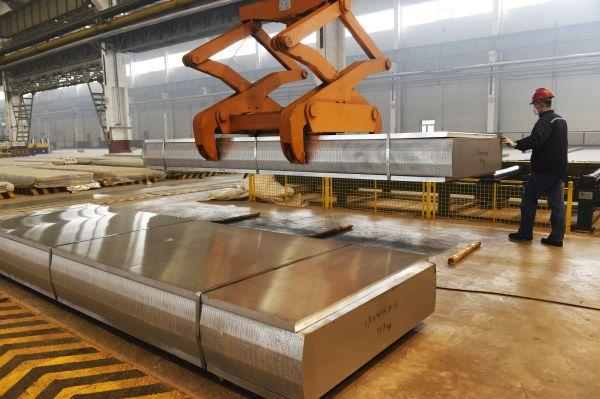 资料图片:2015年12月1日,山东齐星工业铝材有限公司工人在吊装生产的铝扁锭。新华社发(董乃德 摄)