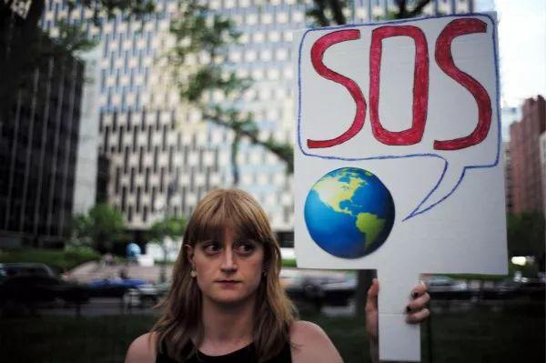 2017年6月1日,纽约一名女子手持标语抗议美国退出《巴黎协定》。新华社/法新