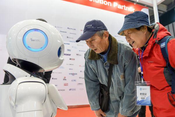 资料图片:2017年12月6日,市民在2017世界智能制造大会展示区IBM展位参观智能互动机器人。新华社记者李博摄