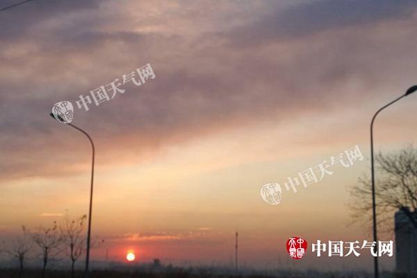 昨晨,北京能见度恶化,初升的太阳将云彩映成粉色。