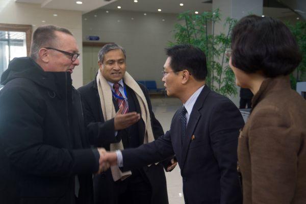 5日,联合国副秘书长费尔特曼(左一)与朝鲜外交官员在平壤国际机场握手。(法新社)